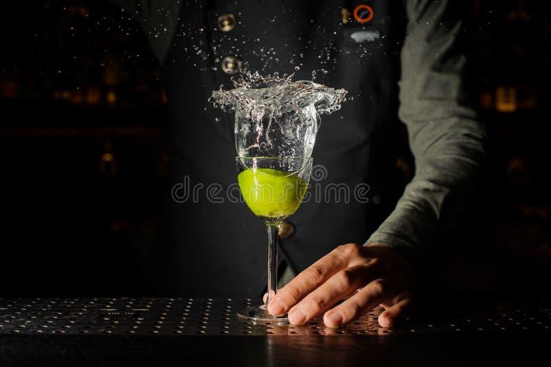Mão do barman que guarda um vidro de espirrar o cocktail de Caipirinha imagem de stock royalty free