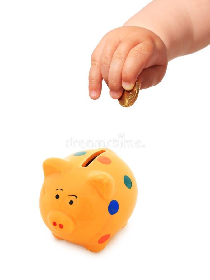 A mão do bebê com moeda e piggybank. fotografia de stock