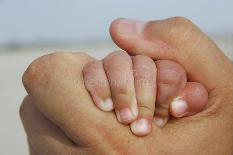 Mão do bebê na mão adulta fotografia de stock