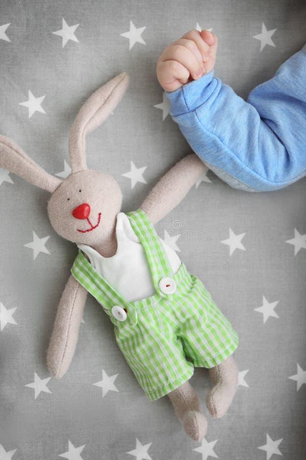 Mão do bebê pequeno bonito com o brinquedo do coelho que encontra-se no berço fotos de stock royalty free