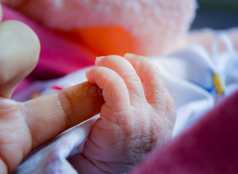 Mão do bebê que guarda o mother& x27; dedo de s na primeira vez quando ele carregado imagem de stock royalty free