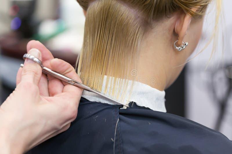 A mão do cabeleireiro que guarda as tesouras que fazem o corte de cabelo fotos de stock royalty free