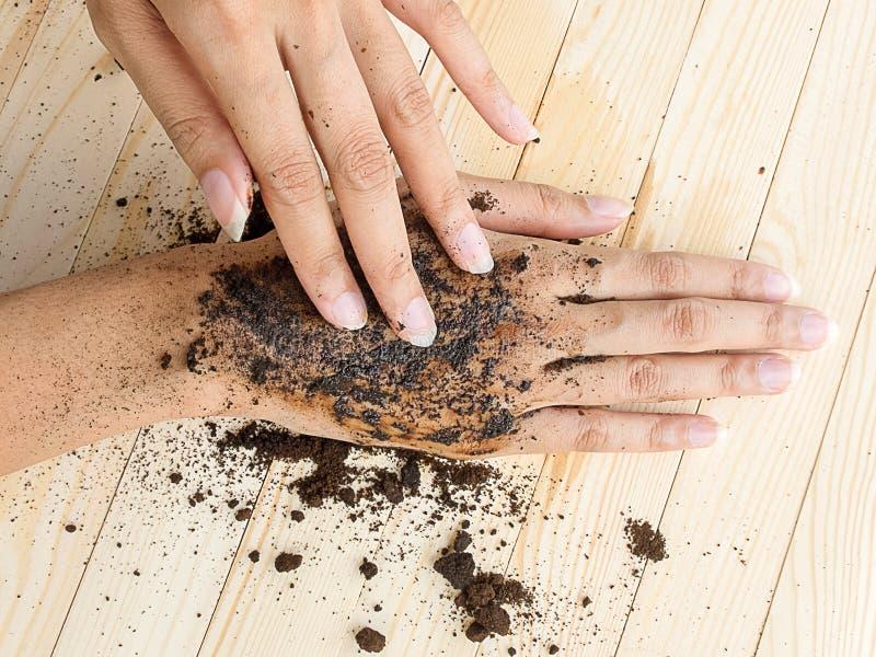 A mão do café esfrega com café à terra no fundo de madeira imagens de stock