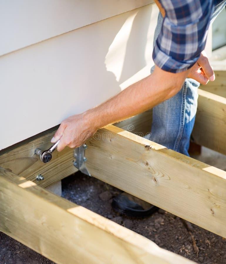 A mão do carpinteiro que aperta o parafuso com chave fotografia de stock