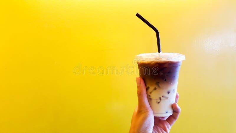 Mão do chá do leite de gelo no fundo amarelo foto de stock