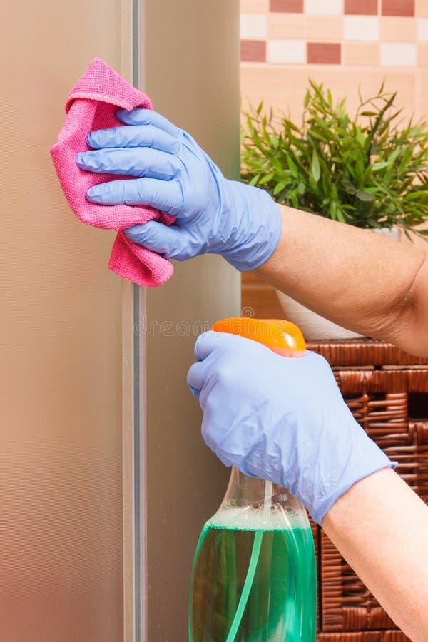 Mão do chuveiro superior do vidro da limpeza da mulher usando o pano do microfiber e o detergente cor-de-rosa, conceito dos dever imagens de stock royalty free