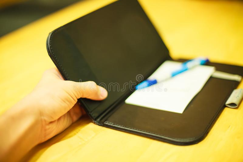 A mão do cliente do foco seletivo recebe o recibo do pagamento da conta na bandeja de couro preta do suporte do dobrador no fundo fotografia de stock royalty free