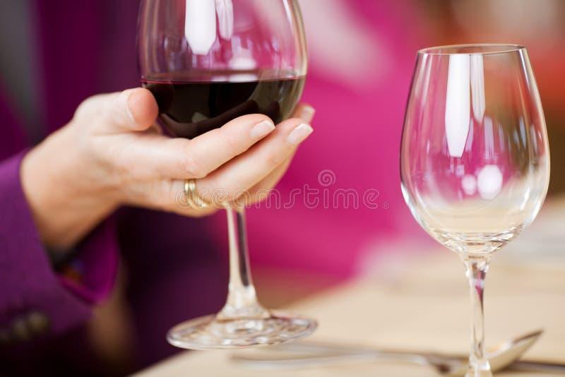 A mão do cliente que guardara o vidro de vinho na tabela do restaurante foto de stock royalty free