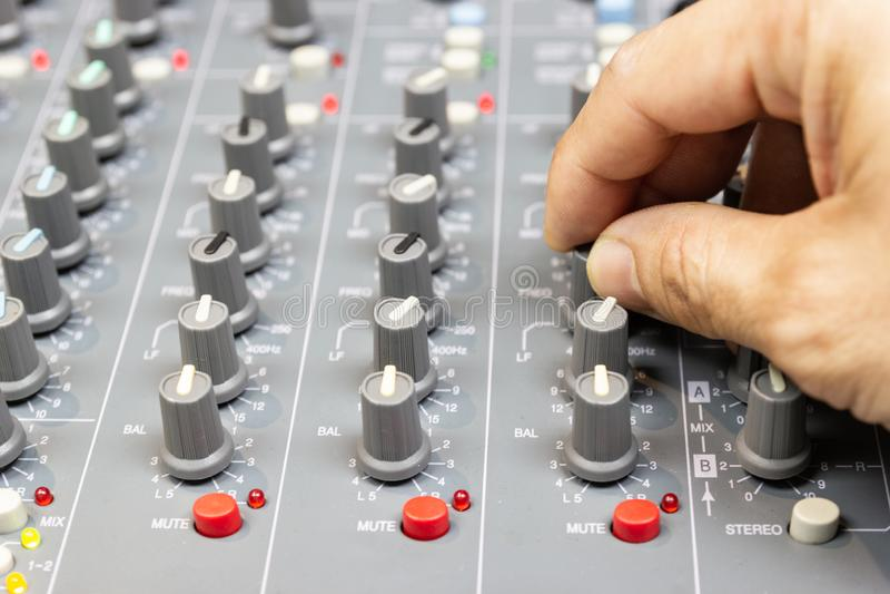 Mão do close-up do console de mistura do controle do homem de um sistema de alta fidelidade grande o equipamento audio imagens de stock