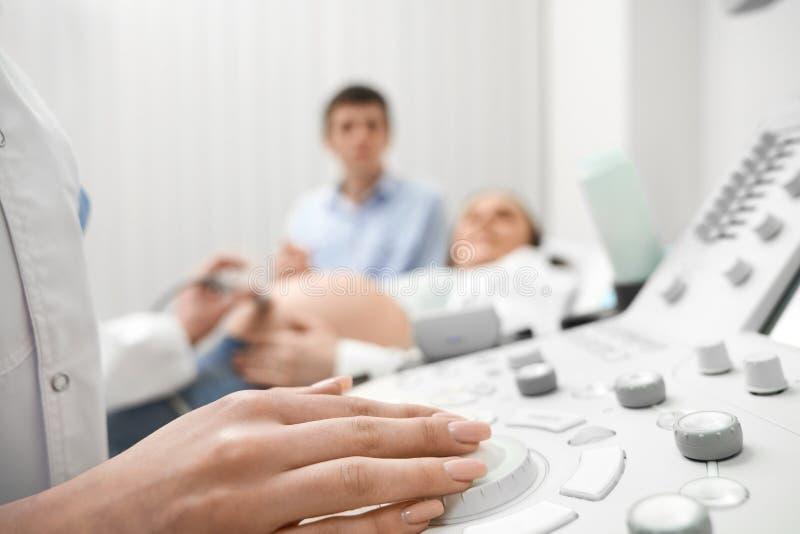 Mão do close up do doutor fêmea na máquina do ultrassom foto de stock