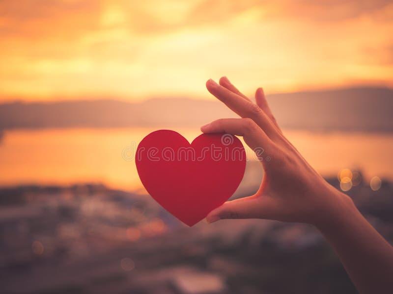 Mão do close up que guarda o coração vermelho durante o fundo do por do sol fotografia de stock royalty free