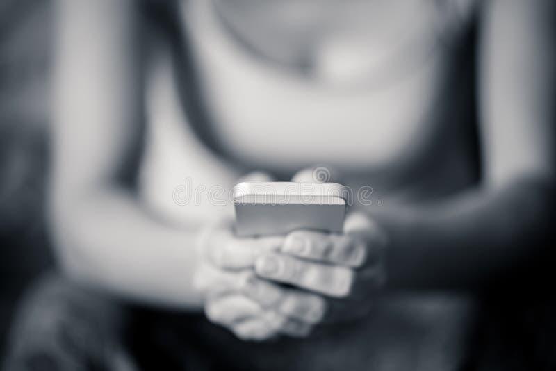 Mão do close-up que guarda o telefone celular fotografia de stock