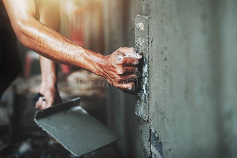 mão do close up do trabalhador que emplastra o cimento na parede para a casa de construção imagem de stock royalty free