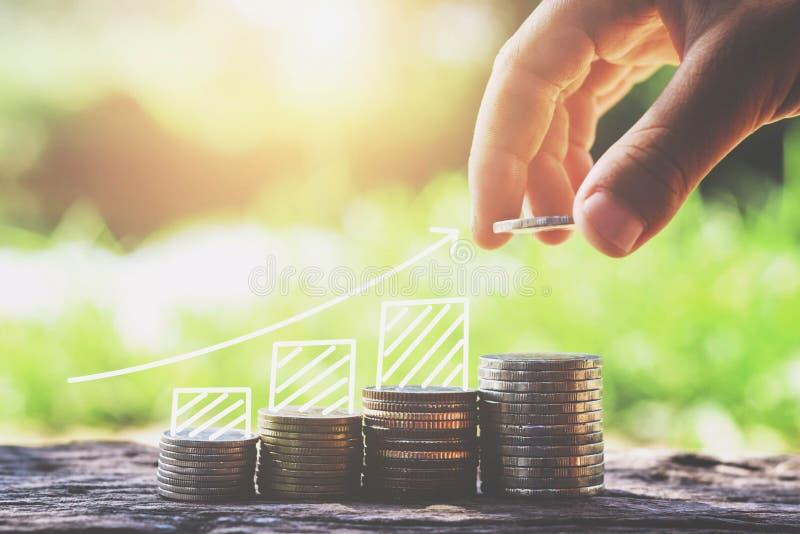 a mão do conceito da economia do dinheiro que põe moedas empilha o negócio crescente fi imagens de stock