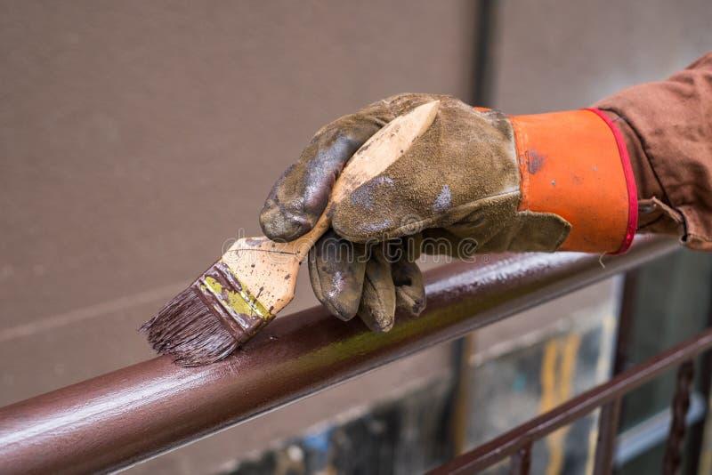 A mão do contratante com escova que construção de cerco do metal da pintura imagens de stock royalty free