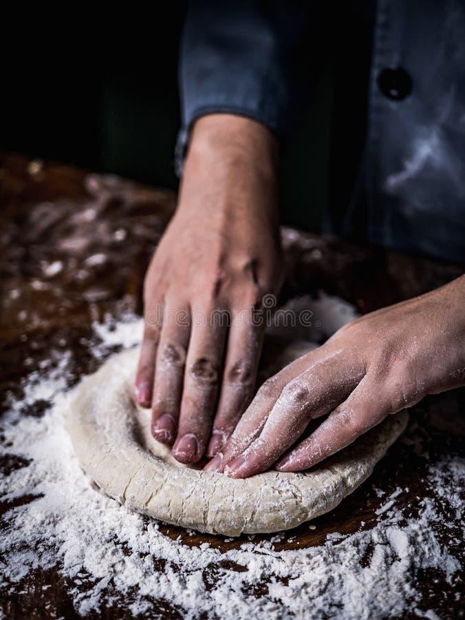 Mão do cozinheiro chefe de pastelaria que amassa a massa crua com polvilhar a farinha branca imagem de stock