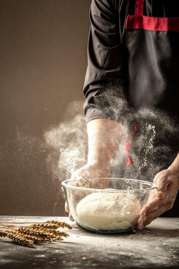 A mão do cozinheiro da pizza com massa e farinha Voo da farinha branca no ar Conceito do alimento imagens de stock