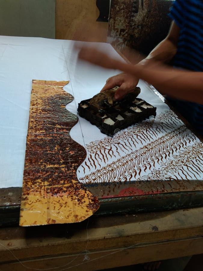 A mão do craftman/artista faz um batik impresso usando o selo imagens de stock