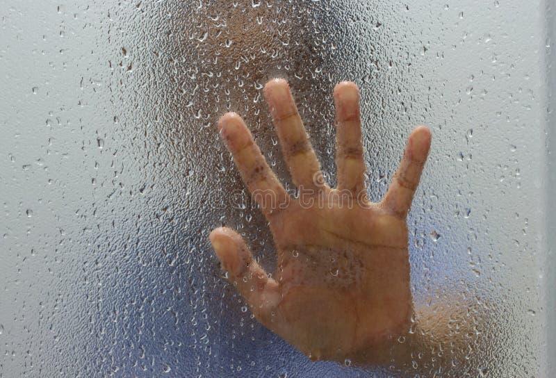 Mão do desconhecido no vidro geado com gota da água fotografia de stock royalty free