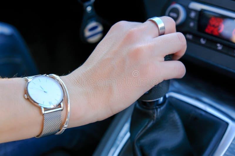 Mão do deslocador da engrenagem da terra arrendada da mulher, condução da transmissão manual fotografia de stock royalty free