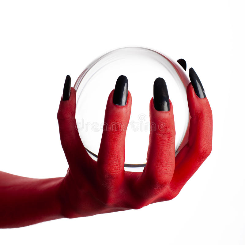 Mão do diabo que prende a esfera de cristal. foto de stock royalty free