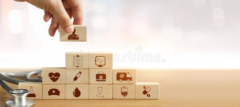 Mão do doutor da medicina que guarda o empilhamento do bloco de madeira foto de stock