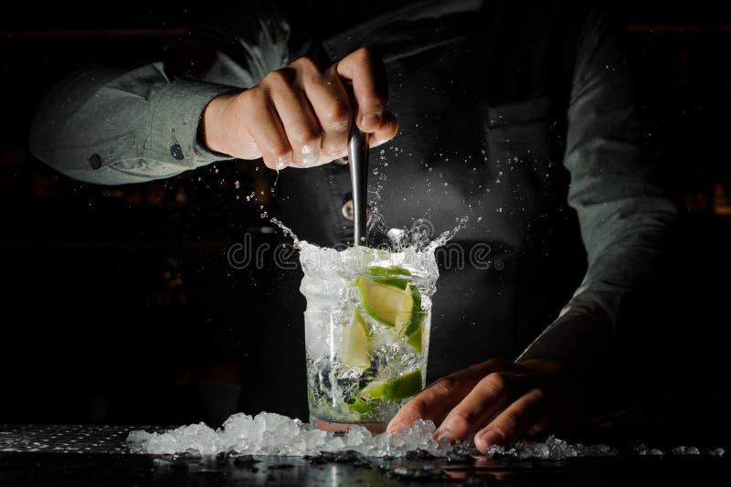 Mão do empregado de bar que espreme o suco fresco do cal que faz o Caipirinh fotografia de stock