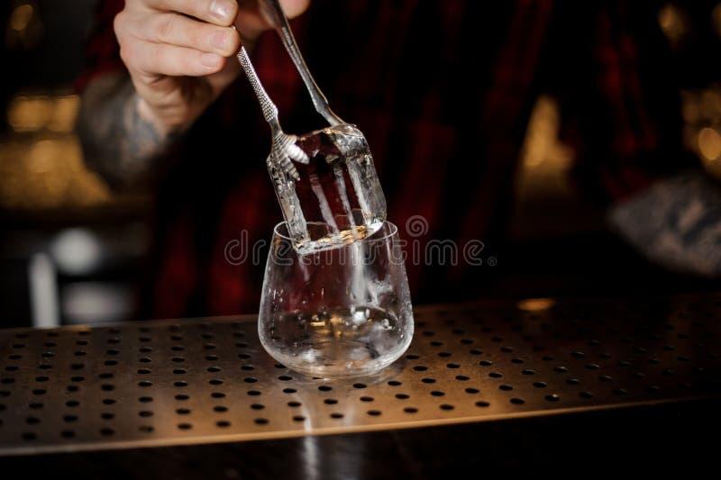 Mão do empregado de bar que põe um cubo de gelo grande em um uísque dof fotografia de stock royalty free