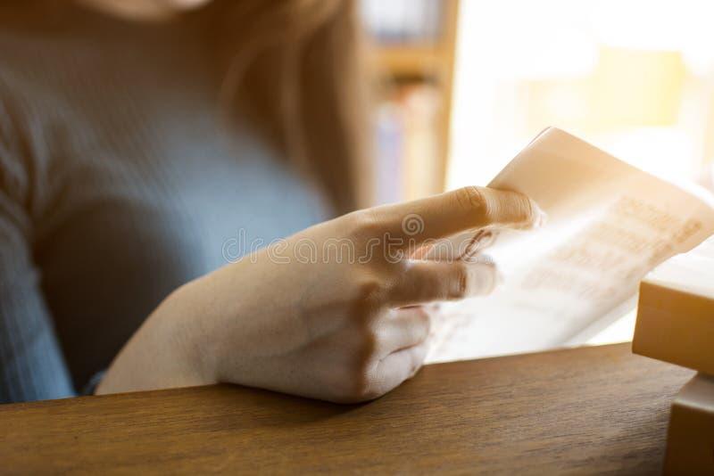 Mão do estudante da moça que guarda um livro à leitura na biblioteca imagem de stock royalty free
