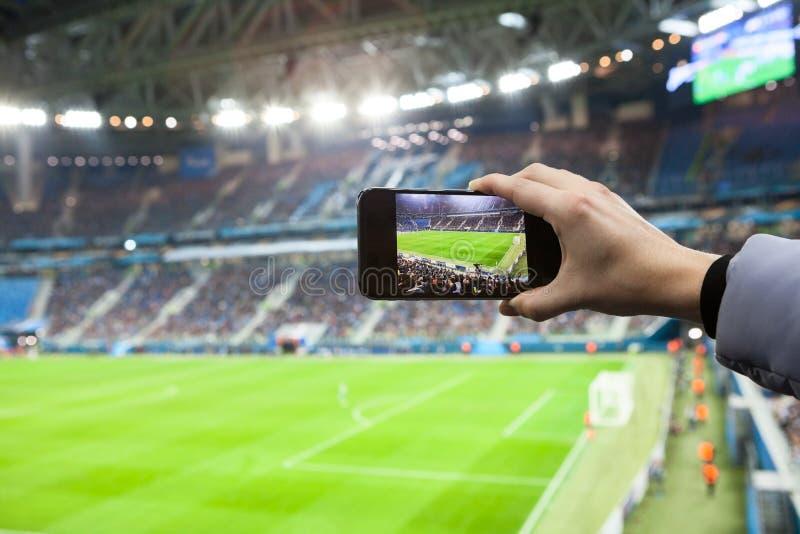 Mão do fã com o smartphone que fotografa o jogo footbal fotos de stock