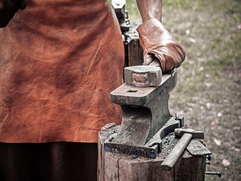 Mão do ferreiro com um martelo no batente de aço Mão de um ferreiro nas luvas de couro com fim do martelo acima E imagens de stock royalty free