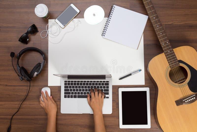 Mão do fundo da mesa de escritório usando uma guitarra acústica e fones de ouvido do portátil foto de stock royalty free