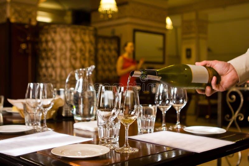 A mão do garçom derrama o vinho branco em um copo de vinho quando uma mulher do sommelier explicar durante testes do vinho fotografia de stock