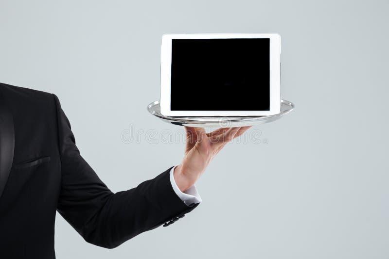Mão do garçom no terno preto que guarda a tabuleta da tela vazia fotos de stock
