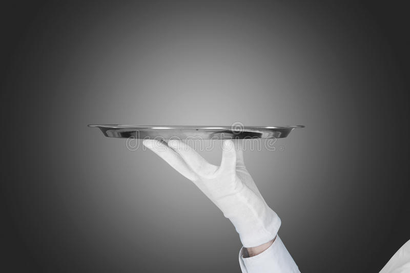 A mão do garçom que guarda a bandeja sobre o fundo cinzento imagens de stock royalty free