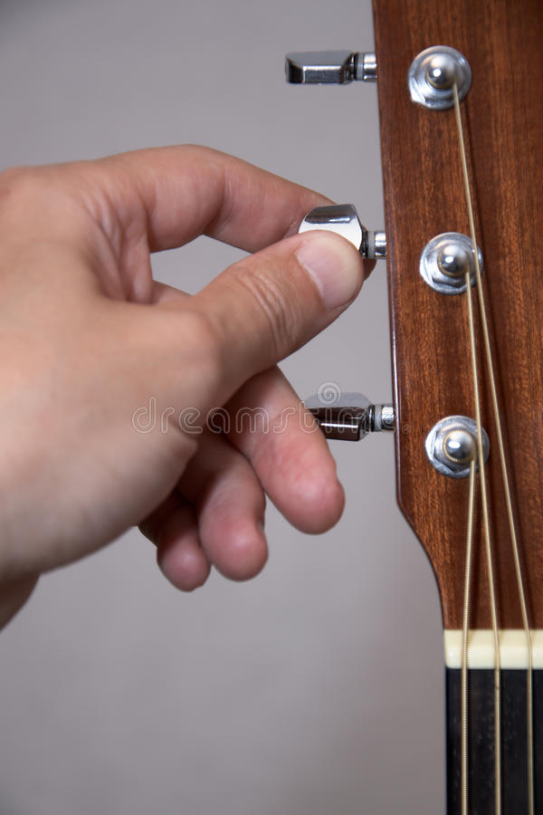 Mão Do Guitarrista Que Ajusta A Guitarra Acústica Fotografia de Stock