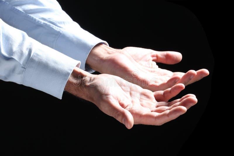 A mão do homem aberto isolada em um fundo cinzento escuro imagens de stock royalty free