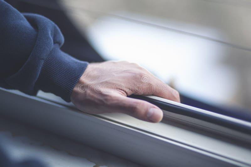 A mão do homem abre a janela fotos de stock