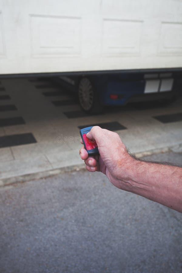 A mão do homem abre a porta da garagem com controlo a distância imagens de stock royalty free