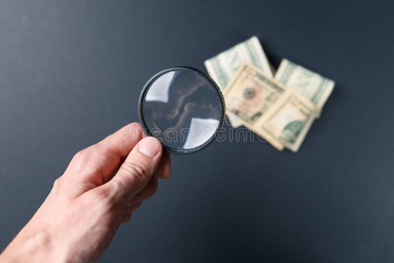 A mão do homem com lupa e dinheiro no fundo preto Moeda de papel Procurando o dinheiro Conceito da busca fotografia de stock royalty free