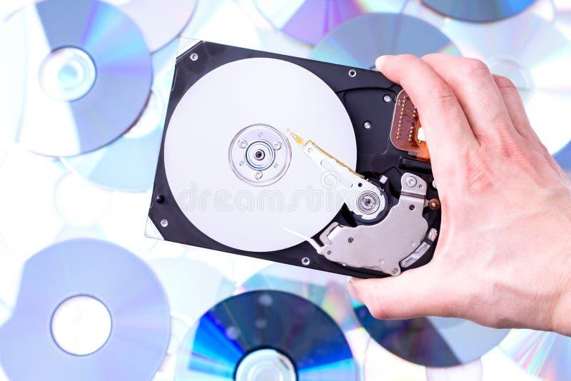 A mão do homem com movimentação de disco rígido sobre o fundo do CD fotos de stock
