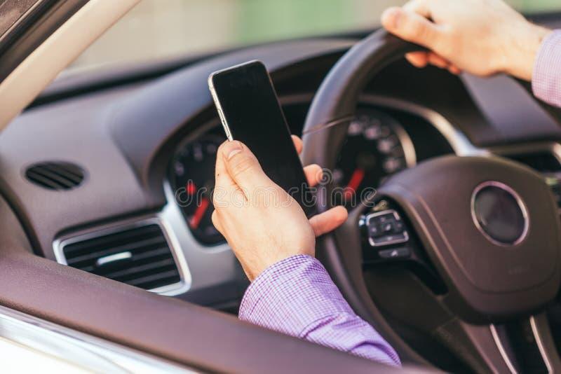 Mão do homem com o smartphone que conduz o carro imagem de stock royalty free