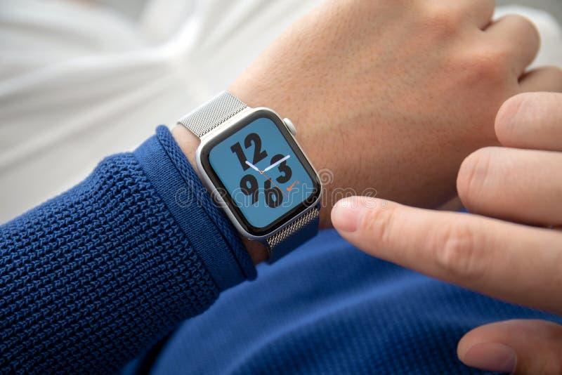 Mão do homem com série 4 Nike Watch Face do relógio de Apple fotografia de stock