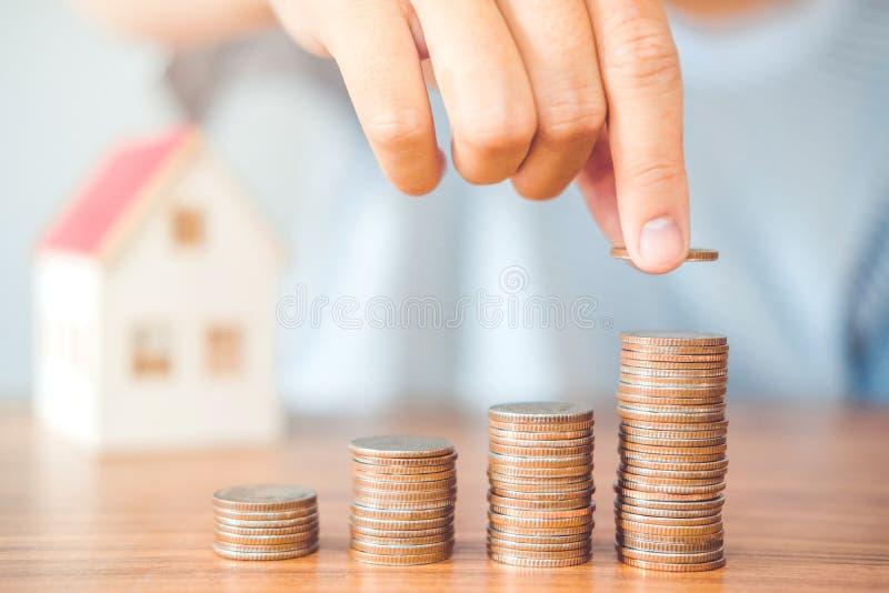 Mão do homem do conceito do dinheiro da economia que põe a finança da pilha da moeda para o botão fotos de stock royalty free