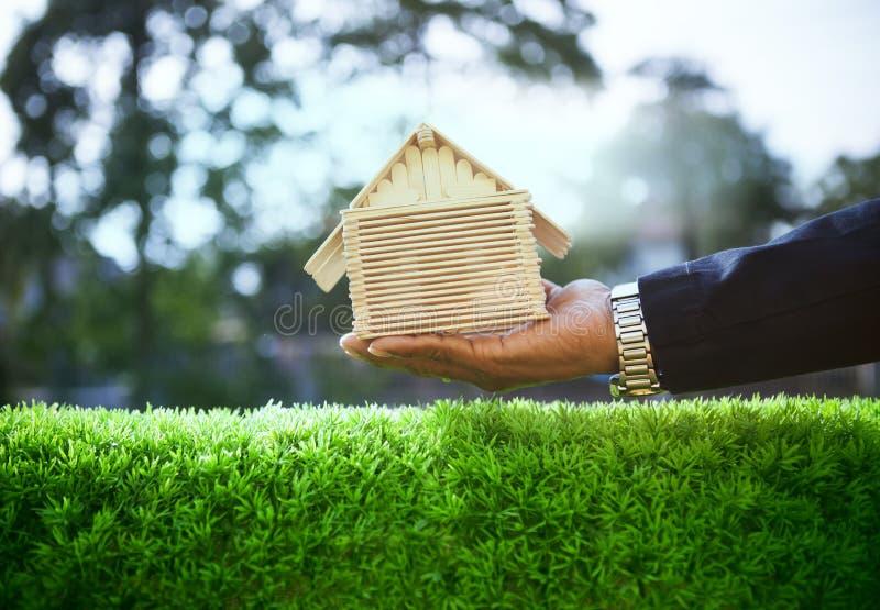 A mão do homem de negócio e a casa de madeira modelam no gra verde bonito imagem de stock