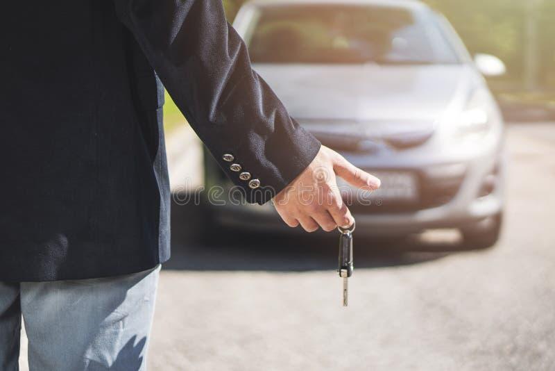 Mão do homem de negócio que guarda a chave do carro fotografia de stock royalty free