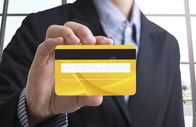 mão do homem de negócio que guarda o cartão de crédito amarelo vazio imagem de stock royalty free