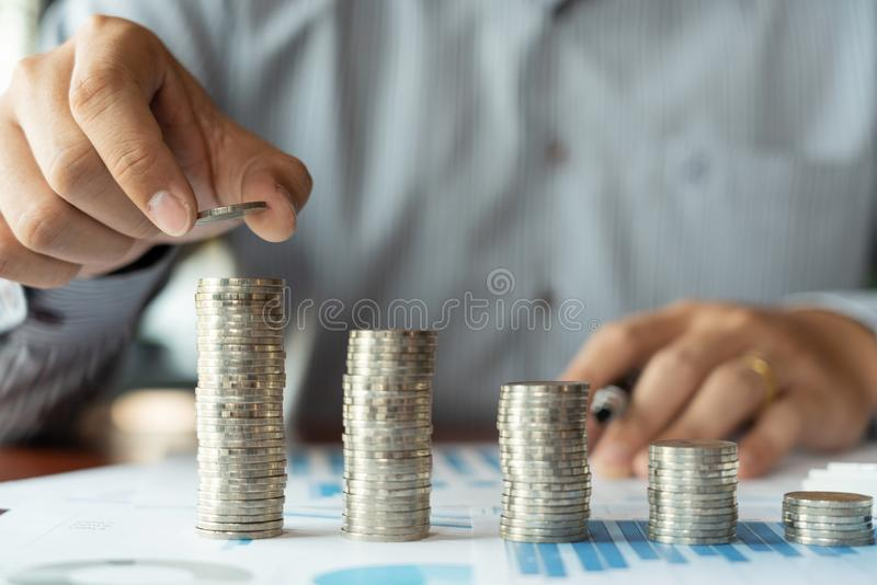 Mão do homem de negócio que põe a pilha da moeda para o investimento do dinheiro da economia do orçamento e a gestão explicando f fotos de stock royalty free