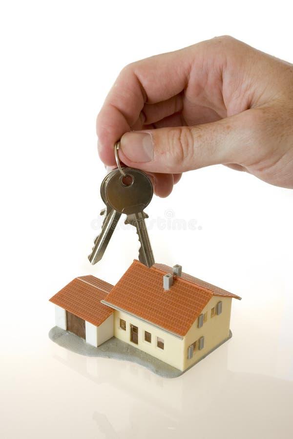 Mão do homem de negócios com chaves e uma casa pequena fotos de stock royalty free