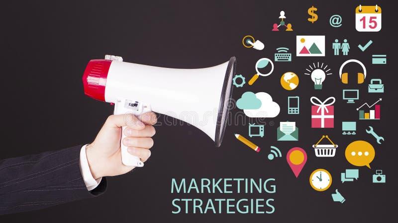 Mão do homem de negócios com o altifalante com os símbolos que voam para fora Estratégias de marketing imagens de stock royalty free